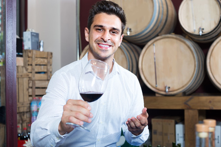 positive  man having wine tasting in cellar with woods