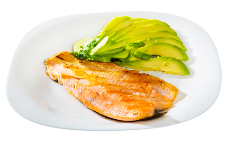 Fried trout fillet served with avocado is tasty dish in the kitchen. Isolated over white background