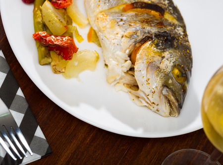 Baked in oven dorado fish with lemon served with vegetables on plate