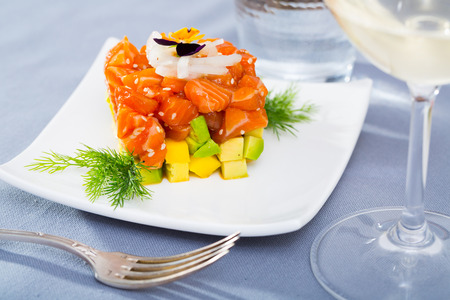 Cube of fresh tartar with salmon, trout, avocado and greens served on plate