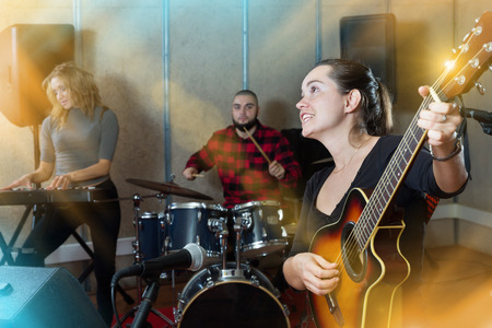 Rehearsal of music band. Positive female guitar player and singer practicing with band members in recording studio Stock fotó