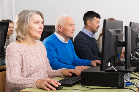 Computer lessons for adults. Group of people of different ages learning to use computers in classroom