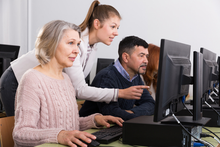 Friendly young female teacher helping mature people to use computer during computer classes at university