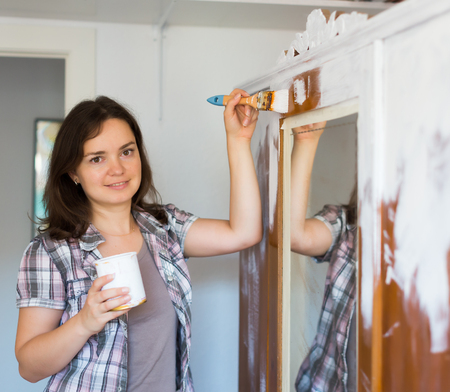 Happy woman makes repairs in the apartment and  paints closet Banque d'images - 118438227