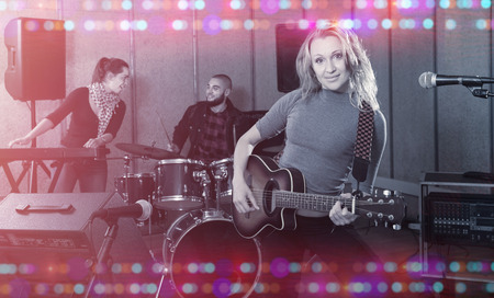 Portrait of excited young blonde girl rock singer with guitar during rehearsal with male drummer and female keyboardist in studio