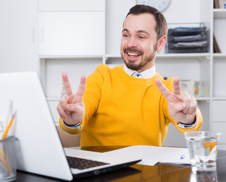 Smiling man communicate by video with partners on laptop at office