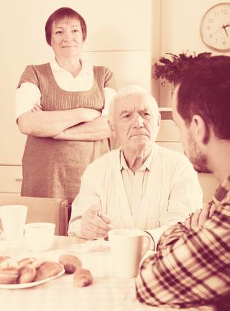 Elderly grandparents talking seriously and instructs grandson in presence of grandmother
