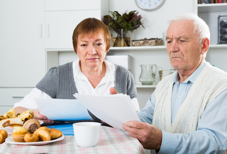 Elderly couple carefully consider contract before signing at table at home