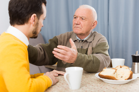 Elderly father teaches and instructs his son at table at home