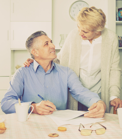 Cheerful positive smiling mature married couple discuss contract at home and sign important documents