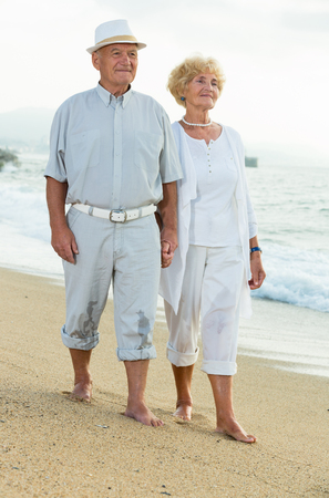 old happy barefoot female and male walking on the beach Banco de Imagens