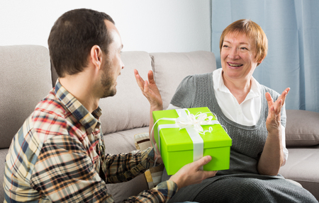Son gives gift in green box for birthday to his mother at home