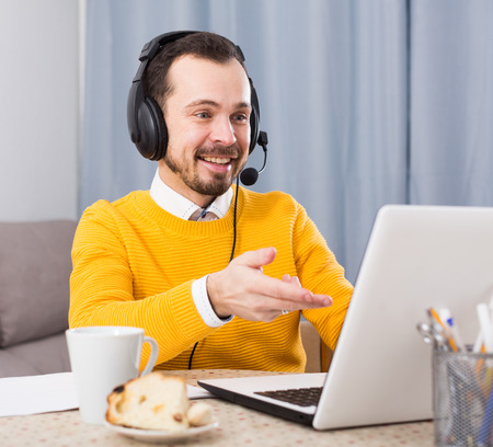 Man distance learning and pleased with decision tasks at home