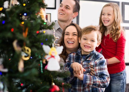 Happy family of four preparing for Christmas together at home