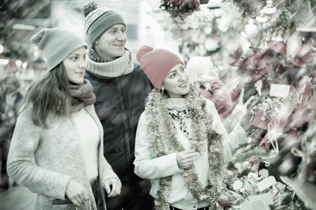 Mother, father and teen girl buying red Euphorbia and  floral decorations  at Christmas fair outdoors Stock Photo