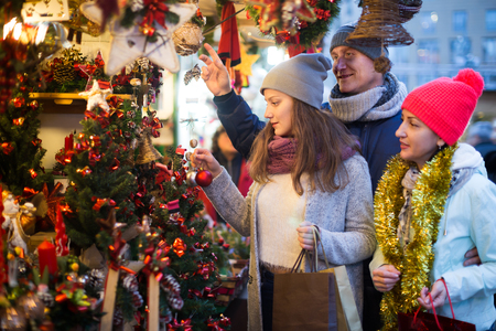 Family with teen girl choosing Christmas decoration at fair Stock Photo