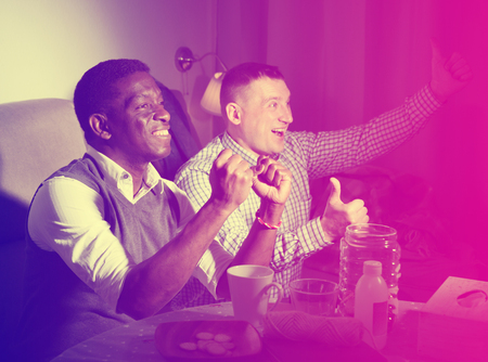 Positive male interracial friends watching football match on tv at home and having fun