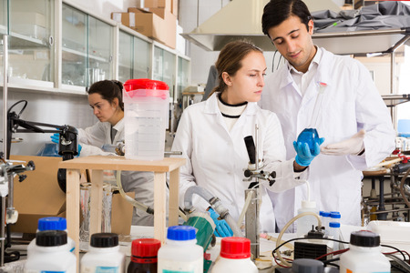 Two young lab technicians discussing while working with reagents in test tubes during chemical experiment Фото со стока