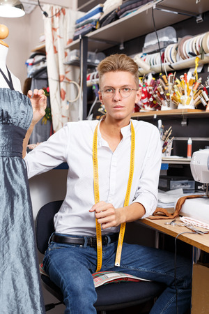 Portrait of blond male dressmaker at his workplace in sewing atelier