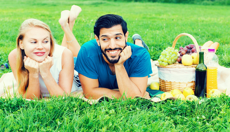 Portrait of  happy cheerful positive couple who are relaxing in time picnic outdoor.
