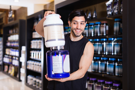 Active muscular smiling positive man showing his power and holding pot of  sport nutrition in shop Stock Photo