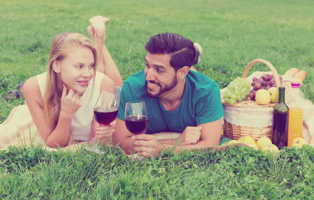 Portrait of man with girlfriend who are talking on picnic outdoor. 写真素材