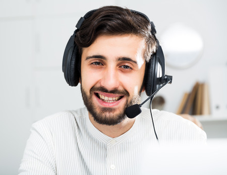 Smiling male business consultant with headphones sitting at deskin in office
