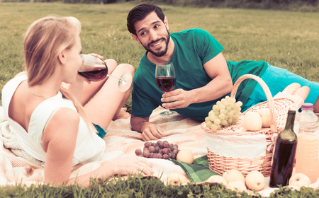 Smiling couple is lying with wineglasses and talking in time picnic outdoor.