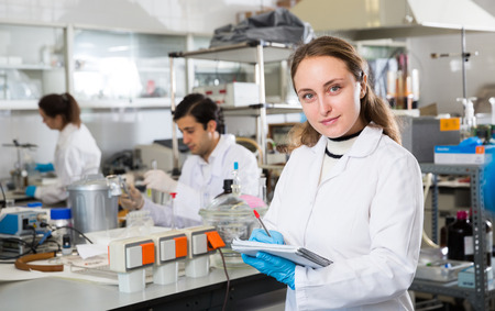 Portrait of young woman lab technician writing report on results of chemical experiments in notebook Stock Photo