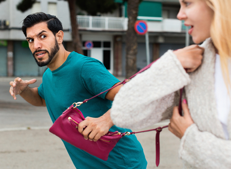 Angry aggressive latino man is stole the handbag from stranger woman on the street. Stockfoto