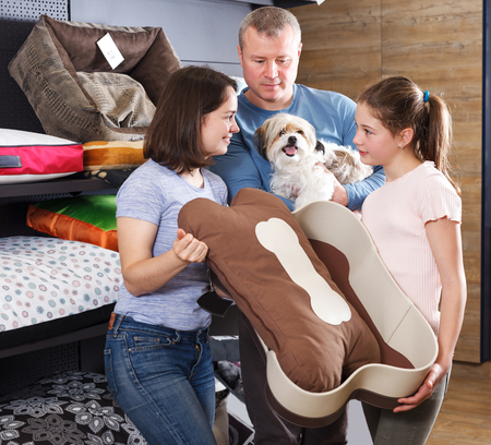 Happy family with preteen daughter visiting pet shop in search of accessories for their dog