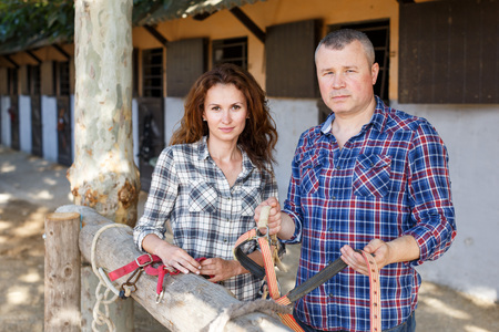 Portrait of smiling couple with girth standing at stable outdoor Stok Fotoğraf