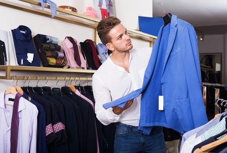 Young positive man purchasing jacket at clothing shop Stock Photo
