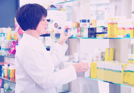 smiling woman pharmacist wearing uniform and working with pills