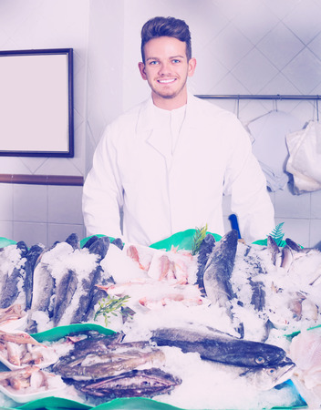 Happy seller posing near display with cooled fish and seafood