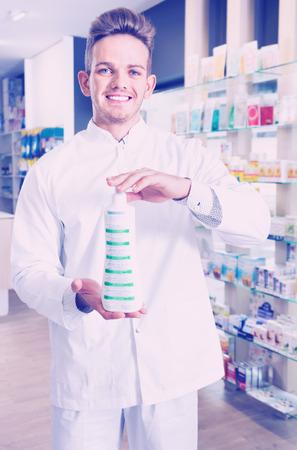Positive diligent glad male pharmacist wearing white coat standing among shelves in drug store Imagens