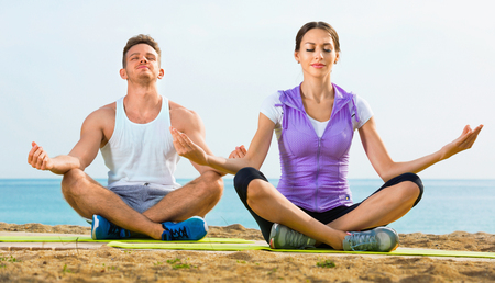 Woman and man sitting cross-legged do yoga poses on beach at daytime