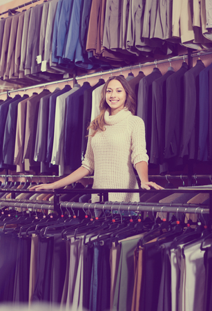 happy spanish female shopping assistant offering various suits in men's cloths store Banco de Imagens