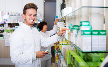 Happy and smiling young team of pharmaceutist and technician working in chemist shop