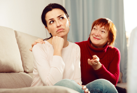 Positive mature female consoling daughter sitting at sofa after quarrel at home