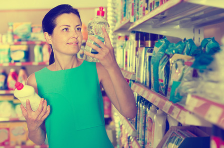 Cheerful female at the shop want to buying fabric softener in bottle Stock Photo