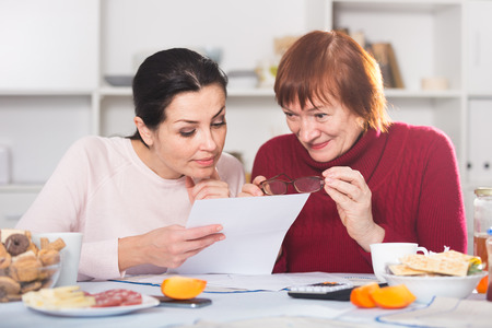 Portrait of mature woman and daughter with documents at table with food 写真素材