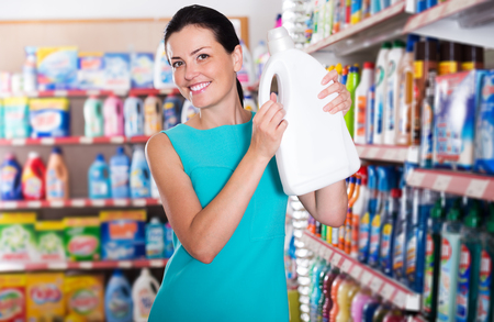 Portrait of happy woman choosing detergent for washing at the supermarket