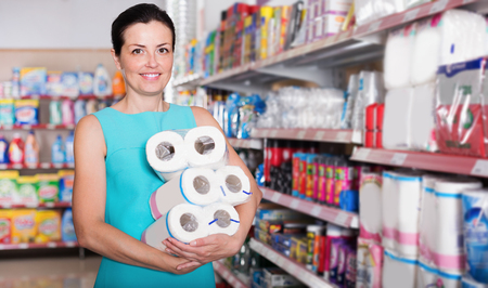 Portrait woman holding pack of toilet paper at the modern supermarket