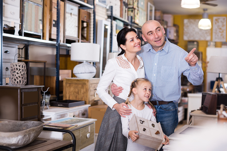 spouses with a daughter  is choosing new furniture for their home in the store.