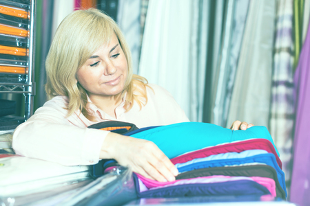 Positive woman customer with sample of bedcover in the textile shop