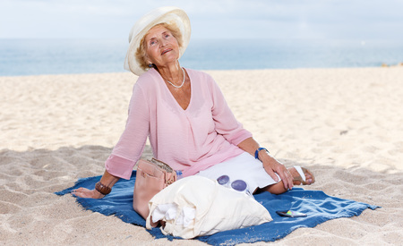 Senior caucasian woman sitting on beach and admiring nature