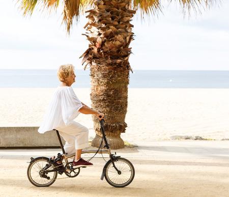 Portrait of happy mature female bicyclist riding on embankment Banco de Imagens