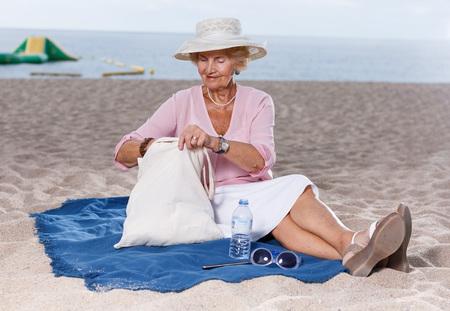 Senior caucasian woman sitting on beach and admiring nature Фото со стока - 118443134