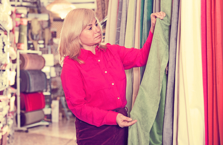 Portrait of smiling mature woman choosing draperies in the store